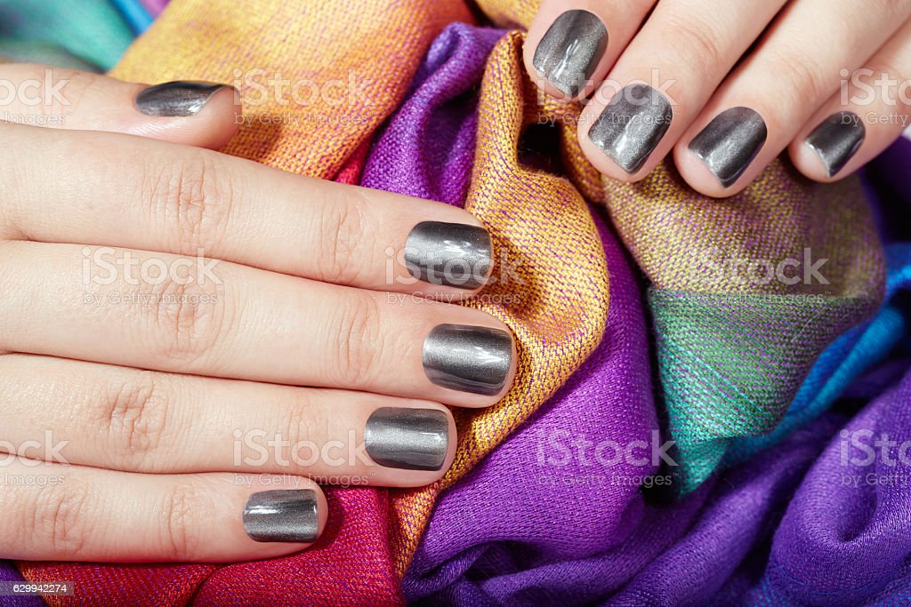 Hands with gray metallic manicured nails on colorful textile...