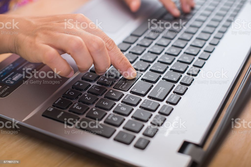 hands with laptop pressing enter button stock photo
