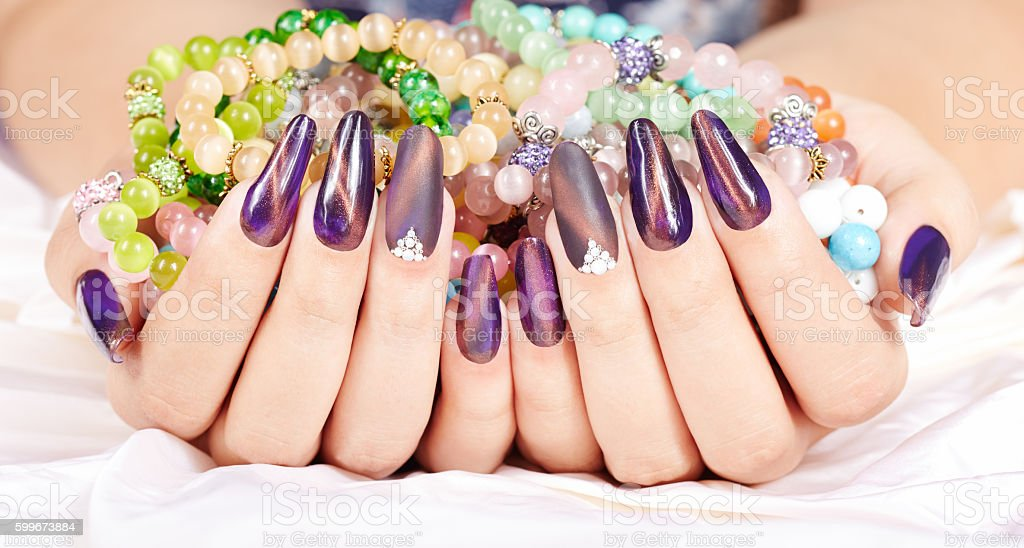 Hands with long artificial manicured nails holding colorful bracelets