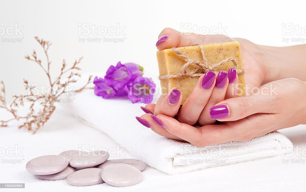 Hands with manicure holding herbal soap royalty-free stock photo