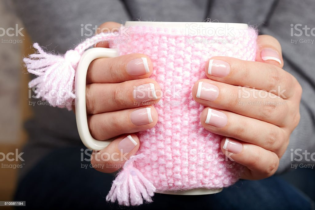 Hands with manicured nails holding a cup with knitted cover stock photo