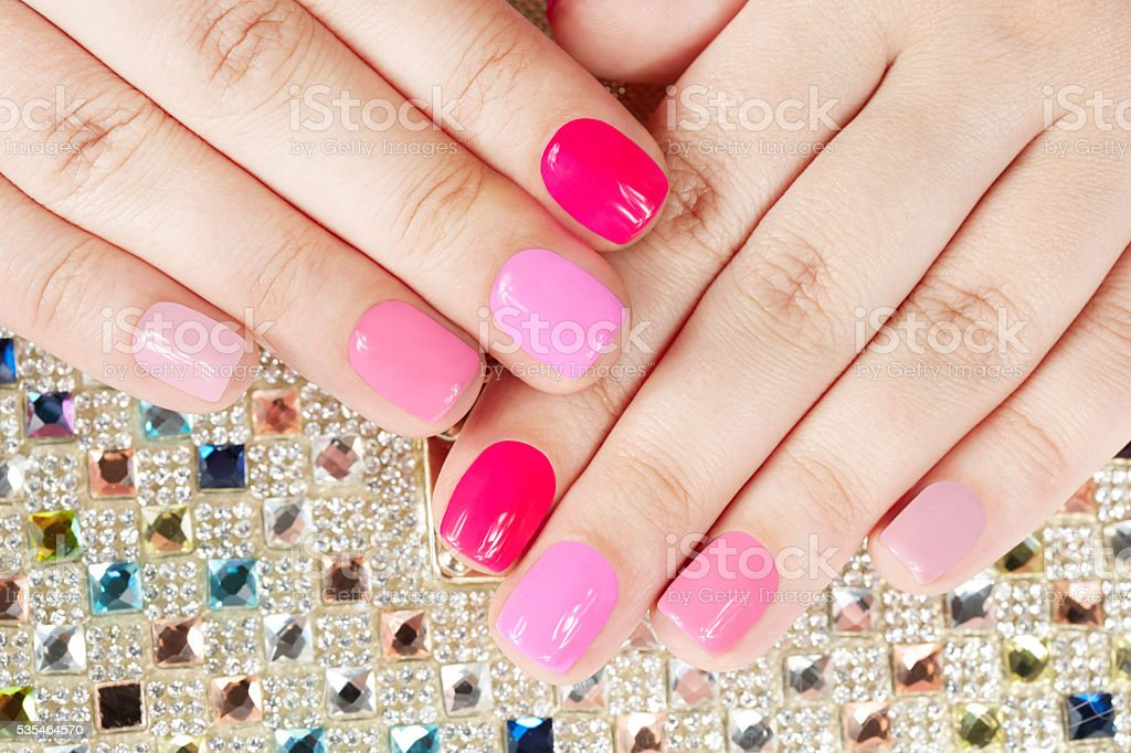 Hands with manicured nails on colorful crystals background stock photo