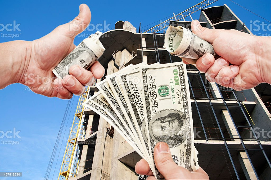 Hands  with notes  dollars against the house under construction stock photo