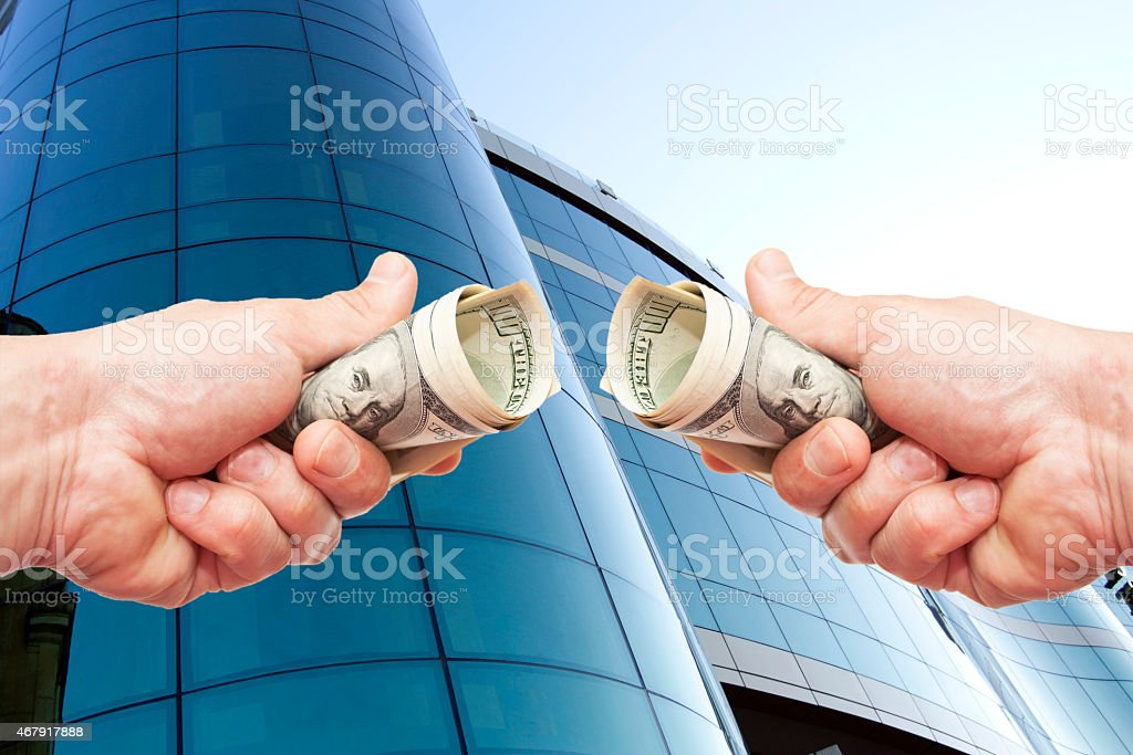 hands with notes of dollars against office building stock photo