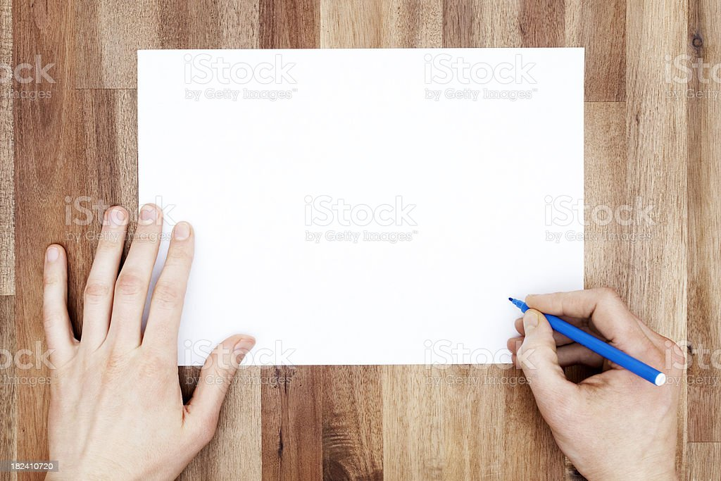Hands with Pen and Piece of Blank Paper on Desk stock photo