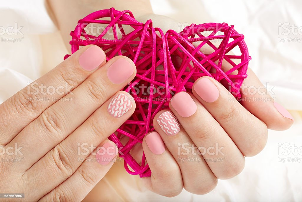 Hands with pink matte manicured nails holding a heart stock photo