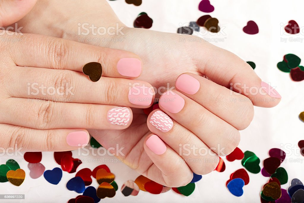 Hands with short pink matte manicured nails