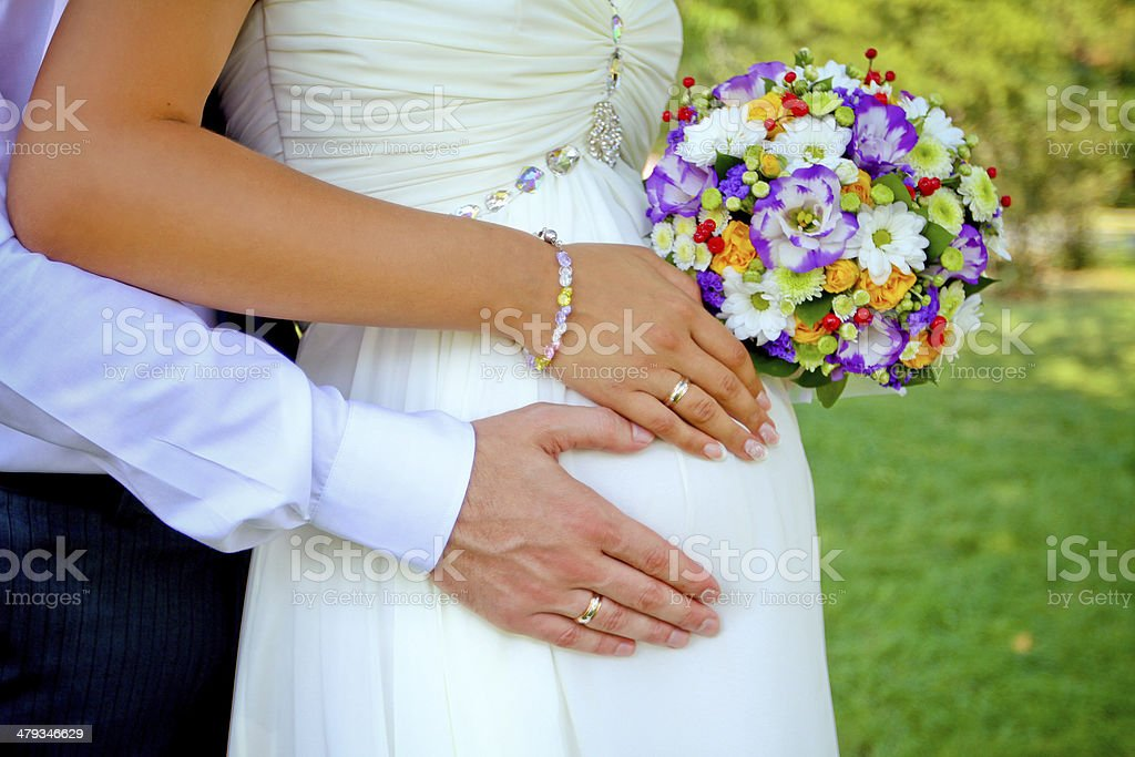 hands with rings and bouquet stock photo