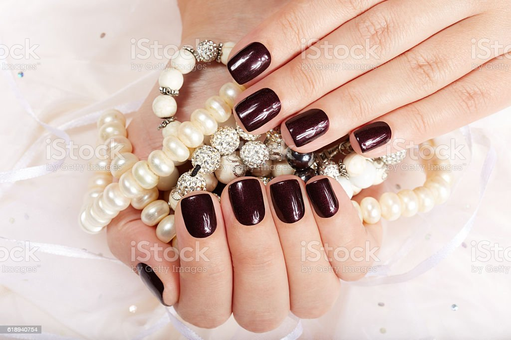 Hands with short manicured nails holding necklaces stock photo