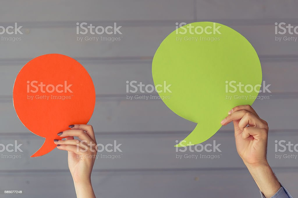 Hands with speech bubbles stock photo