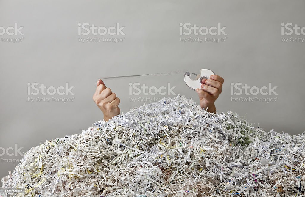 Hands with Tape and Mountain of Shredded Paper stock photo