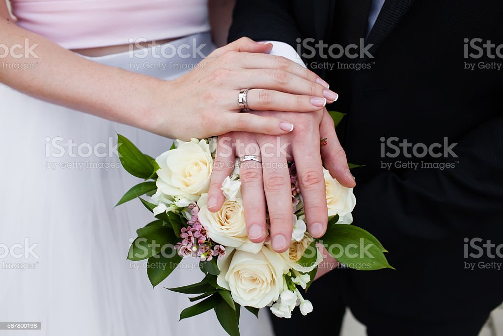 Hands with wedding rings and fower bouquet stock photo