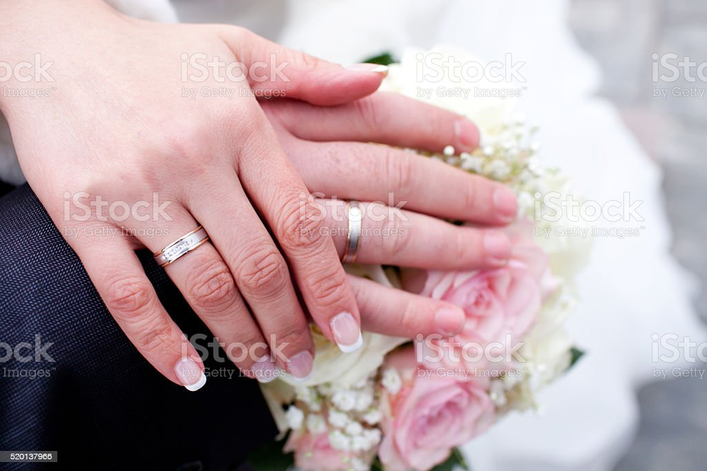 Hands with wedding rings on bridal bouquet stock photo