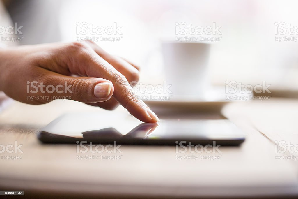 Hands woman using her tablet pc in bar, coffee stock photo