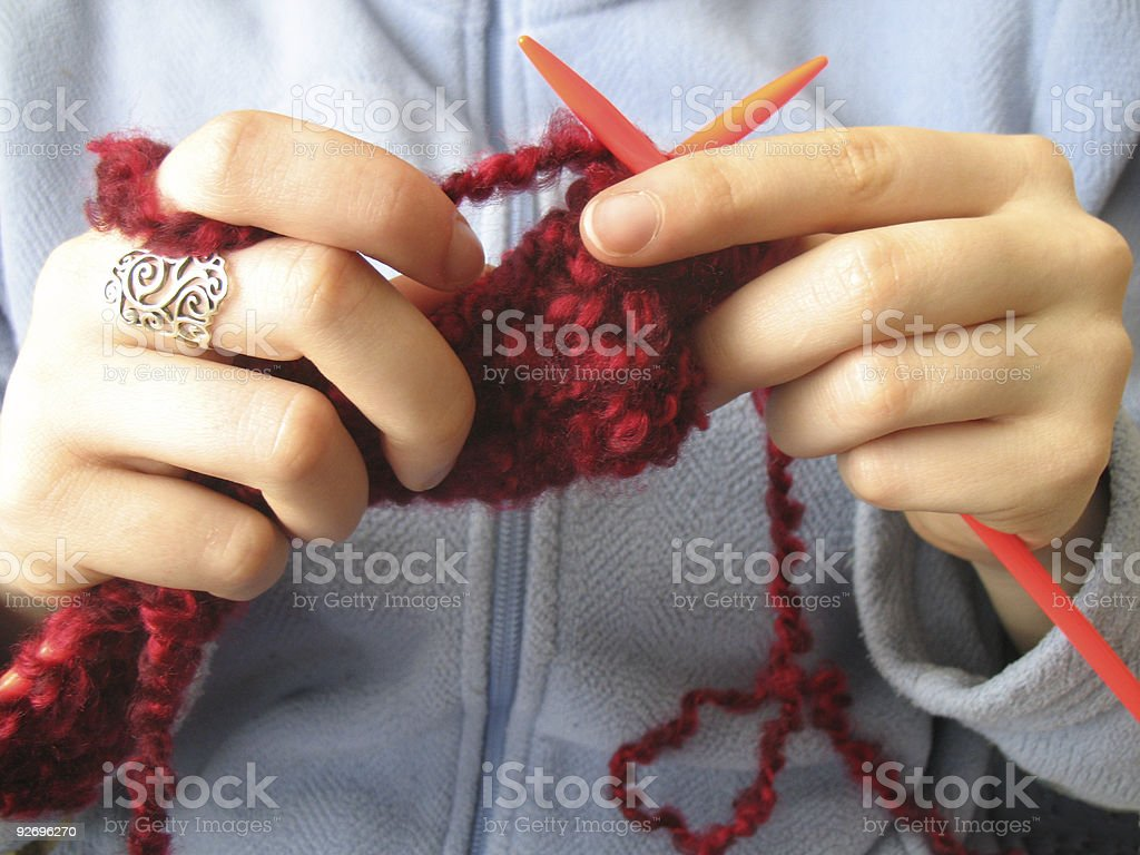 Hands working on a knitting project stock photo