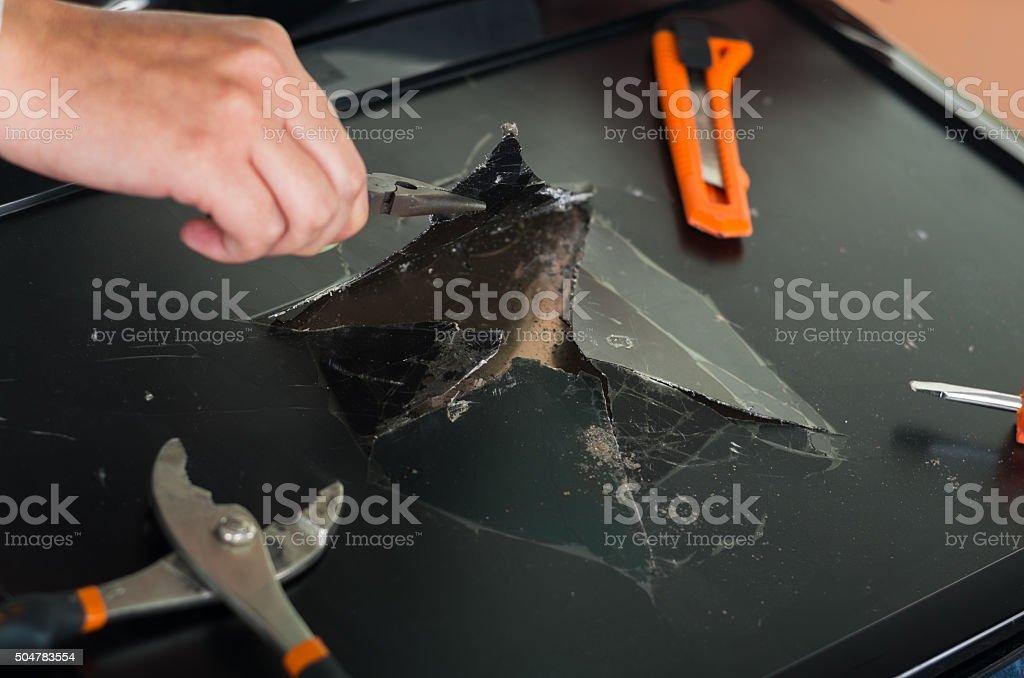 Hands working on broken computer screen using different tools stock photo