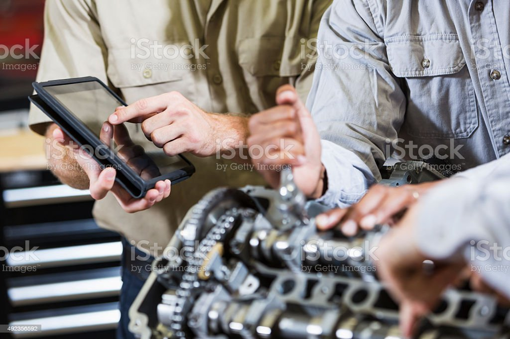 Hands working on car engine stock photo