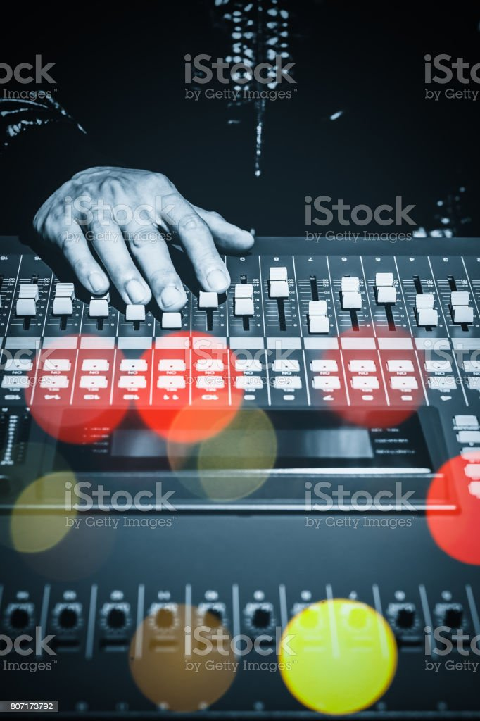 DJ hands working on sound mixer in night club with colourful bokeh stock photo