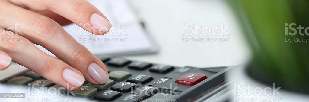 Hands working on the calculator stock photo