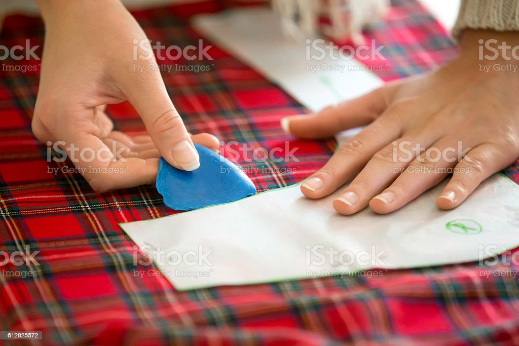 Hands working with a sewing pattern stock photo
