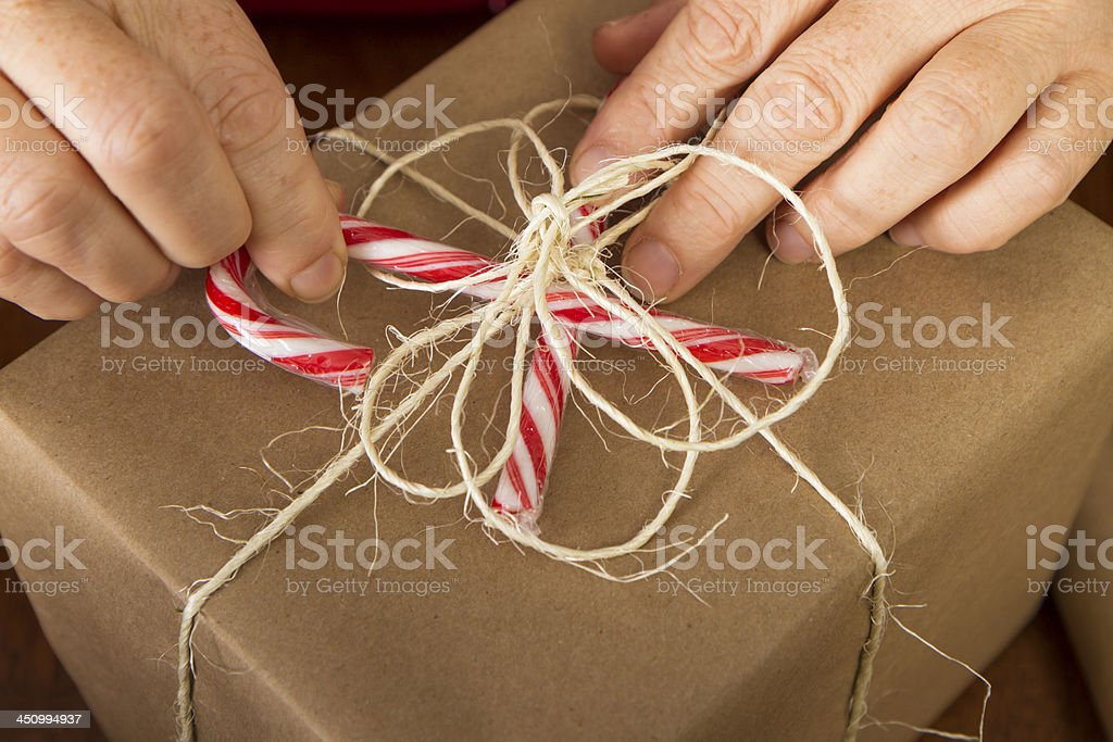 Hands Wrapping Christmas Gifts With Recycled Brown Paper
