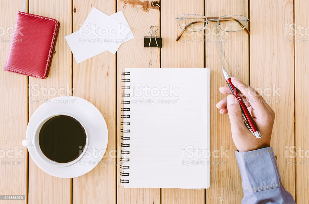 Hands writing on a wooden table with office supplies stock photo