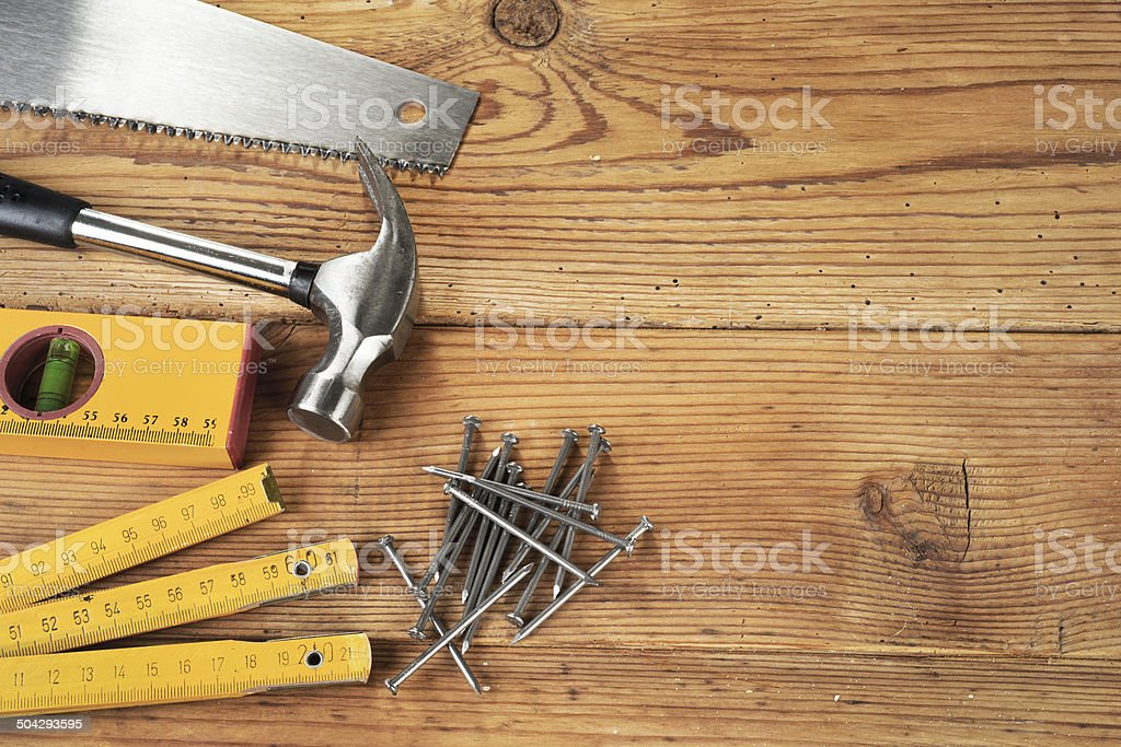 Handsaw, hammer, level, nails and folding ruler on wooden background stock photo