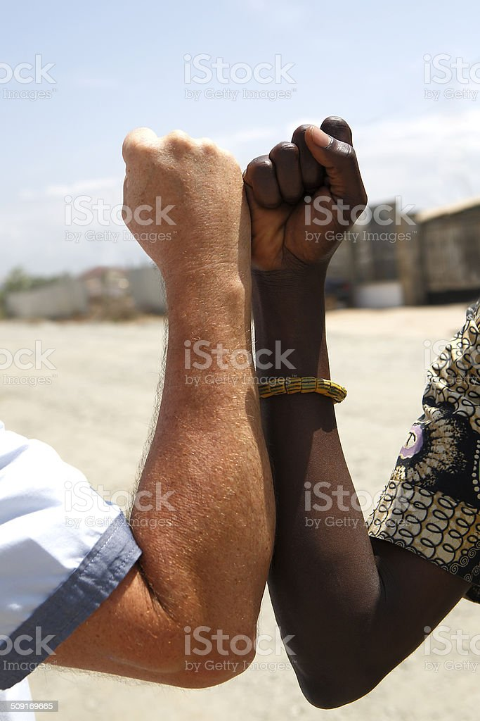 Handshake between a Caucasian and an African stock photo
