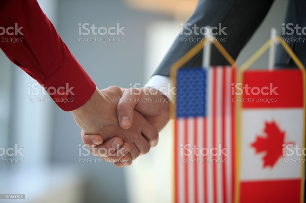 Handshake in front of usa and canada flags stock photo