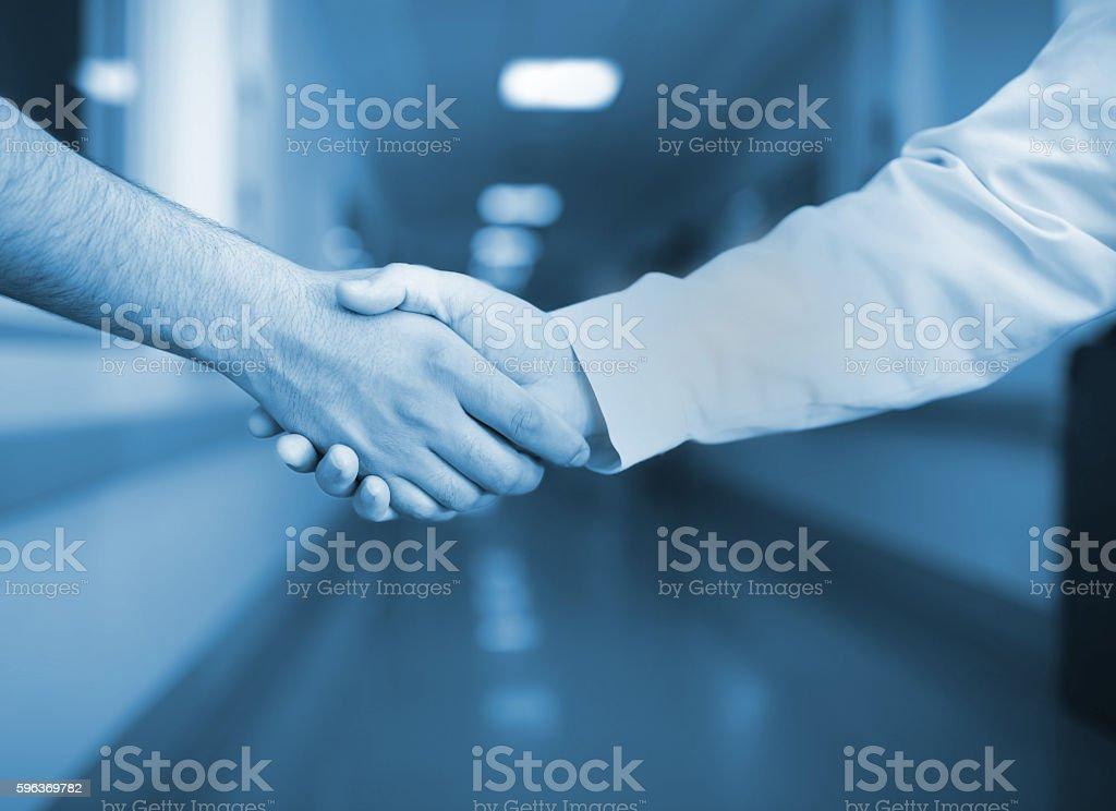 Handshake in the hospital corridor stock photo