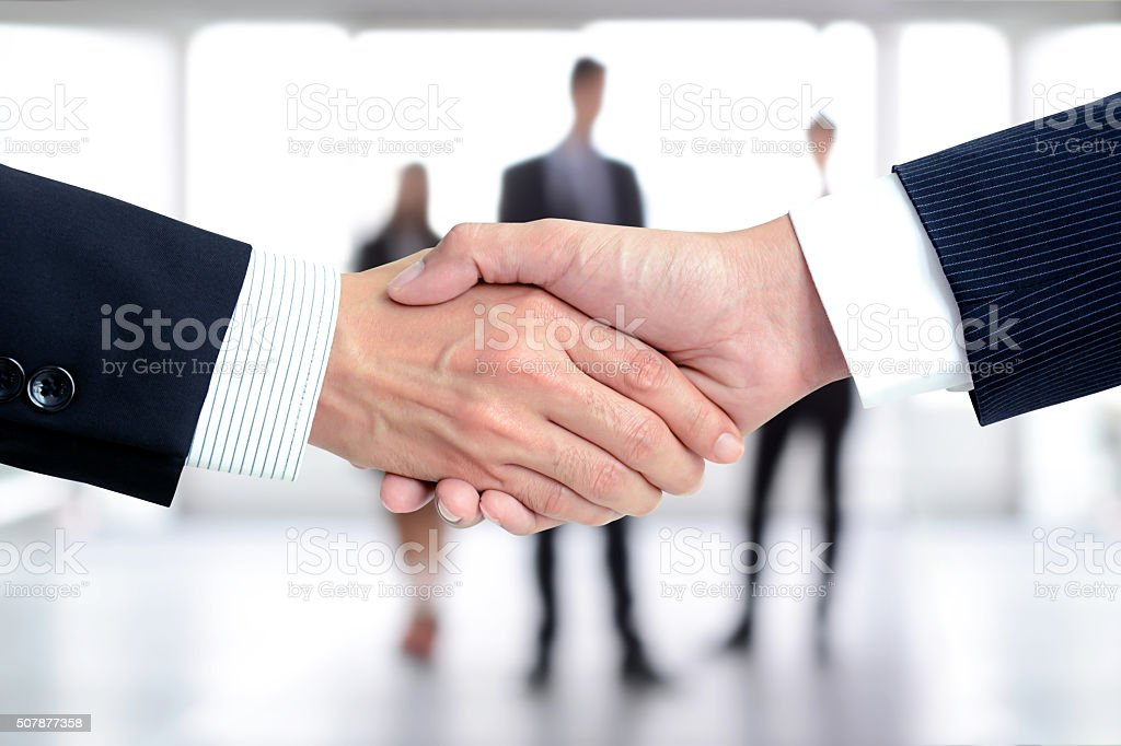 Handshake of businessmen on blur businesspeople background stock photo
