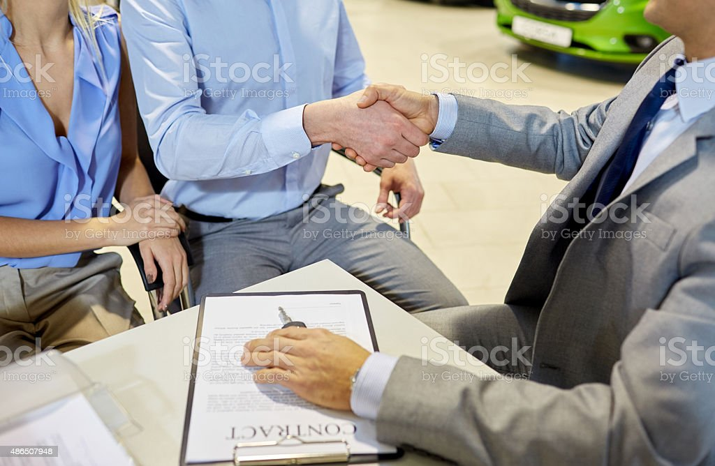 handshake of customer and car dealer in auto salon stock photo