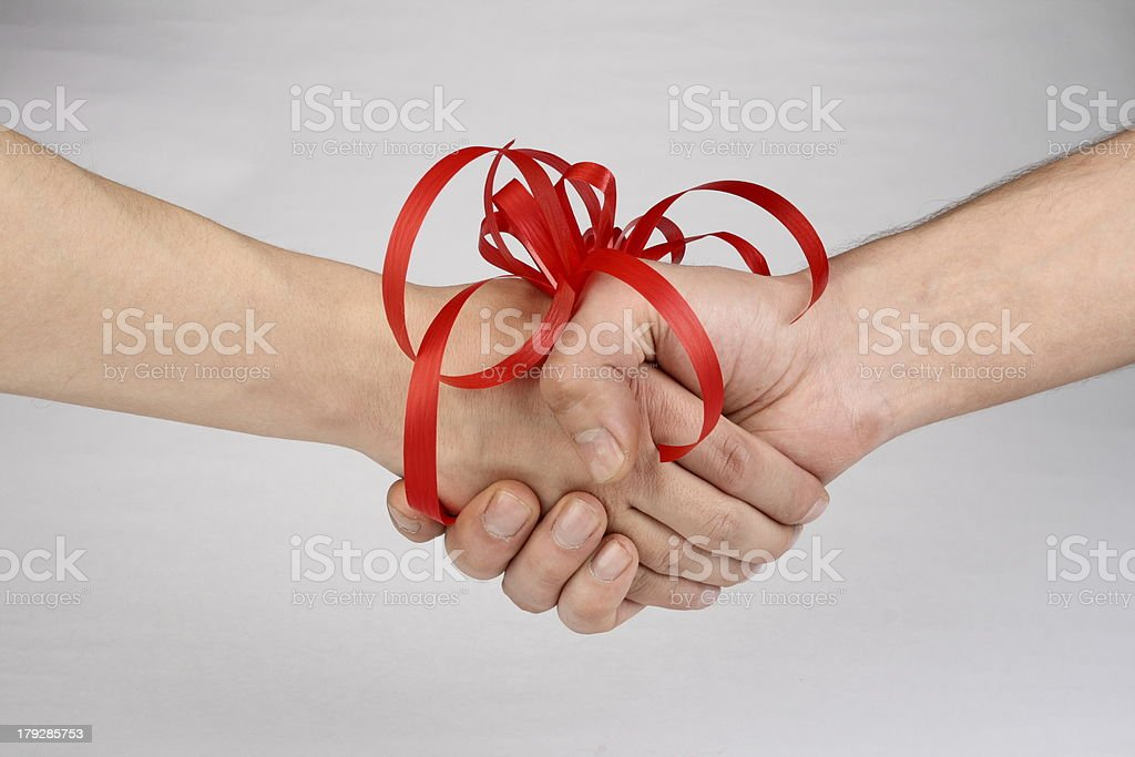 Handshake of friends on grey backgorund stock photo