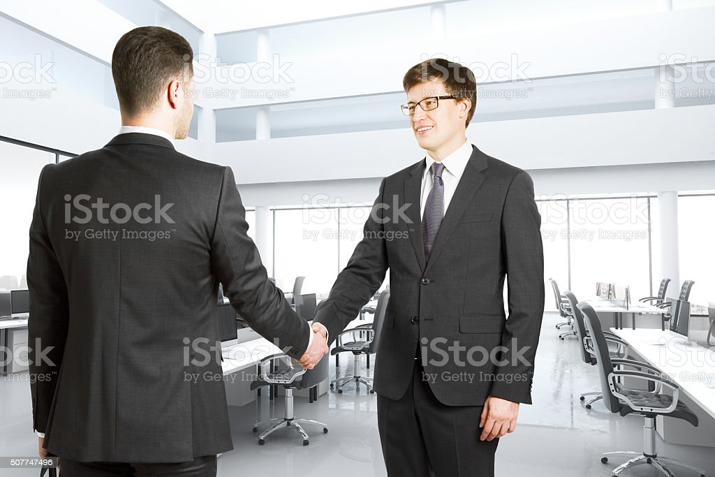 Handshake of two businessmen in a bright modern office stock photo