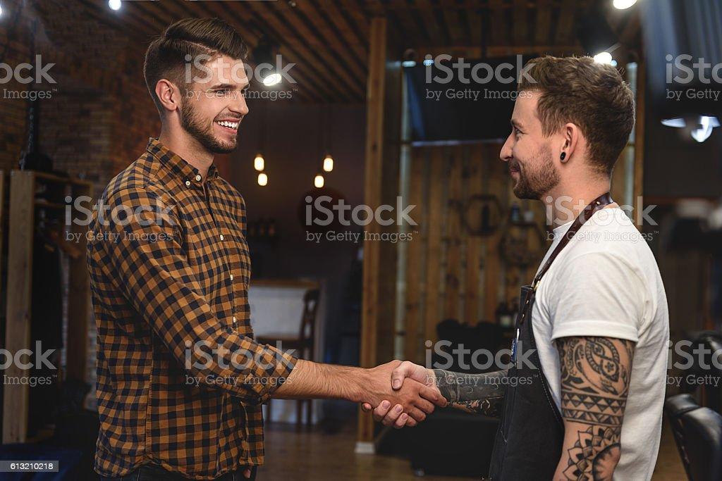 handshake of two guys at barbershop stock photo