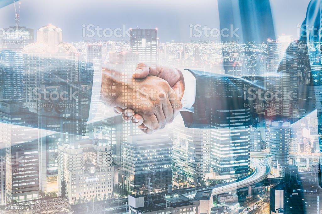 Handshake with skyscrapers stock photo
