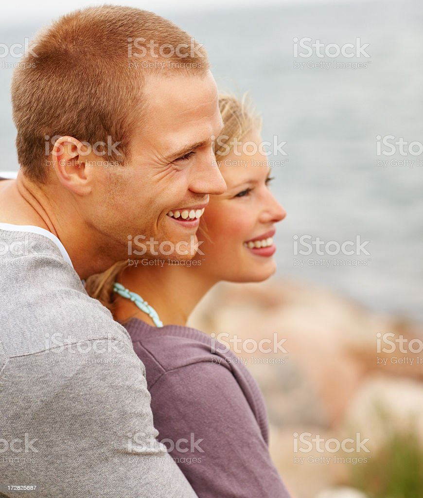 Handsome affectionate young guy embracing his girlfriend outdoors stock photo