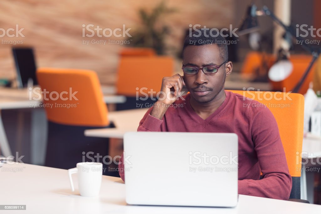 Handsome African American looking at the screen with serious face stock photo