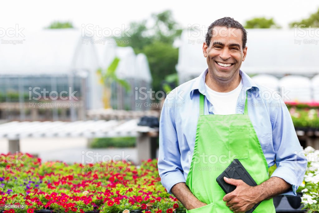 Handsome African American plant nursery owner holding tablet stock photo