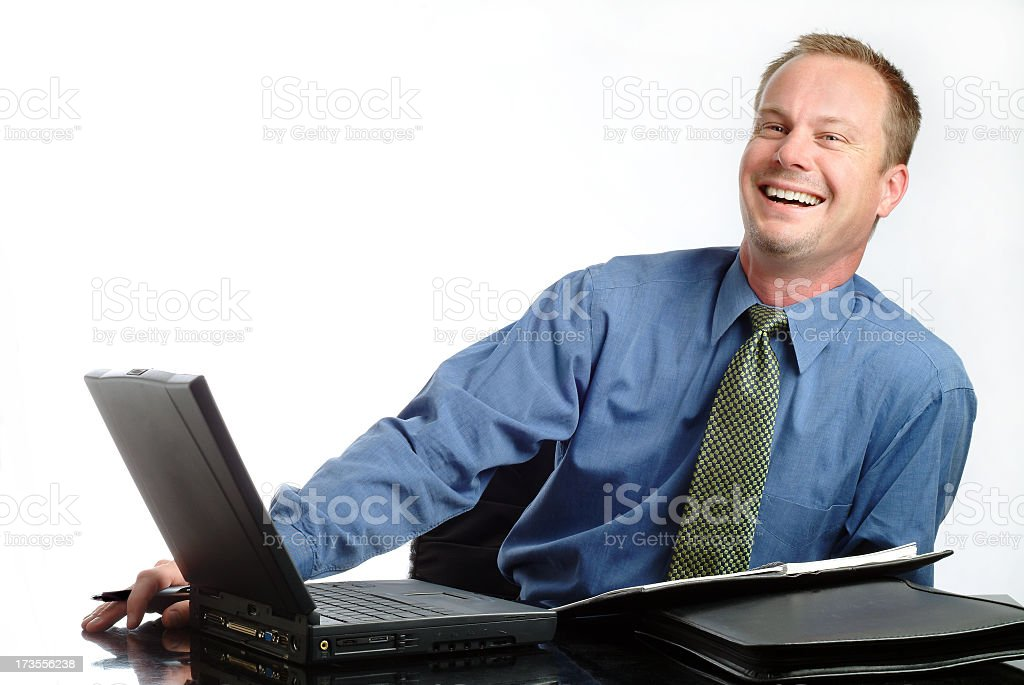 Handsome and Happy Businessman Sitting at His Desk stock photo