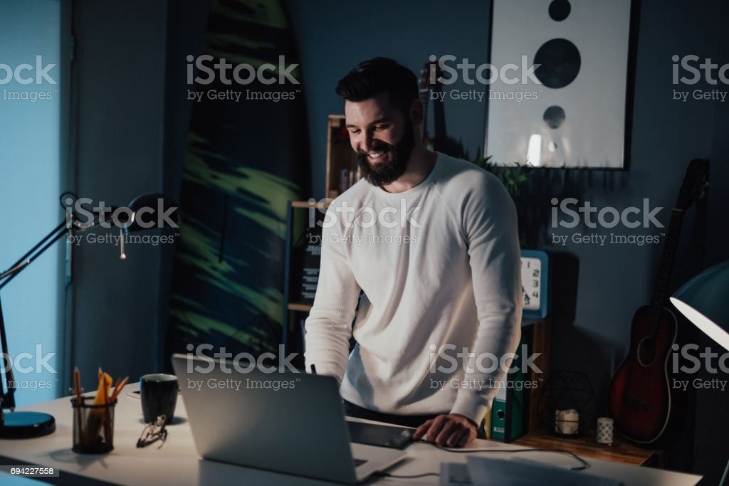 Handsome architect working on the laptop from home office while standing stock photo