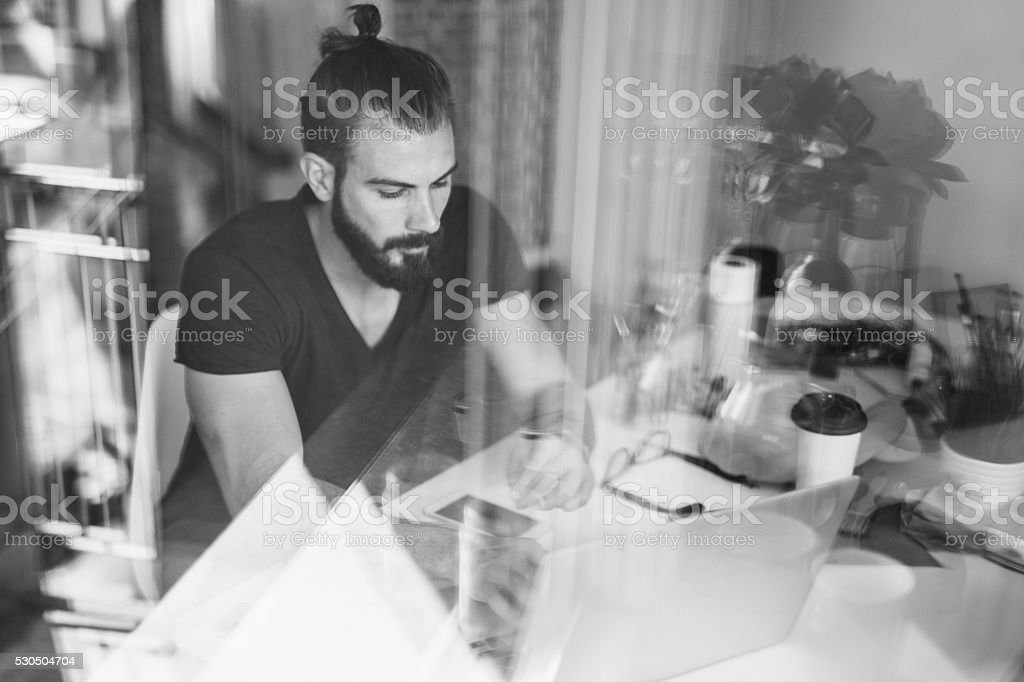 Handsome artist using laptop in his atelier stock photo