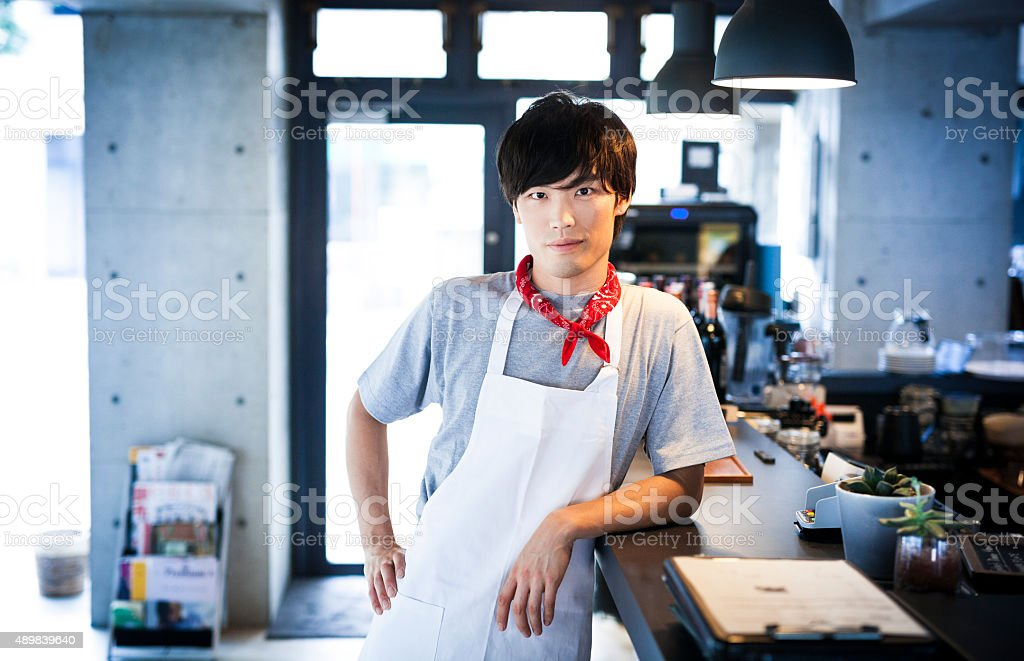Handsome Asian Cook Leaning on a Bar Counter stock photo