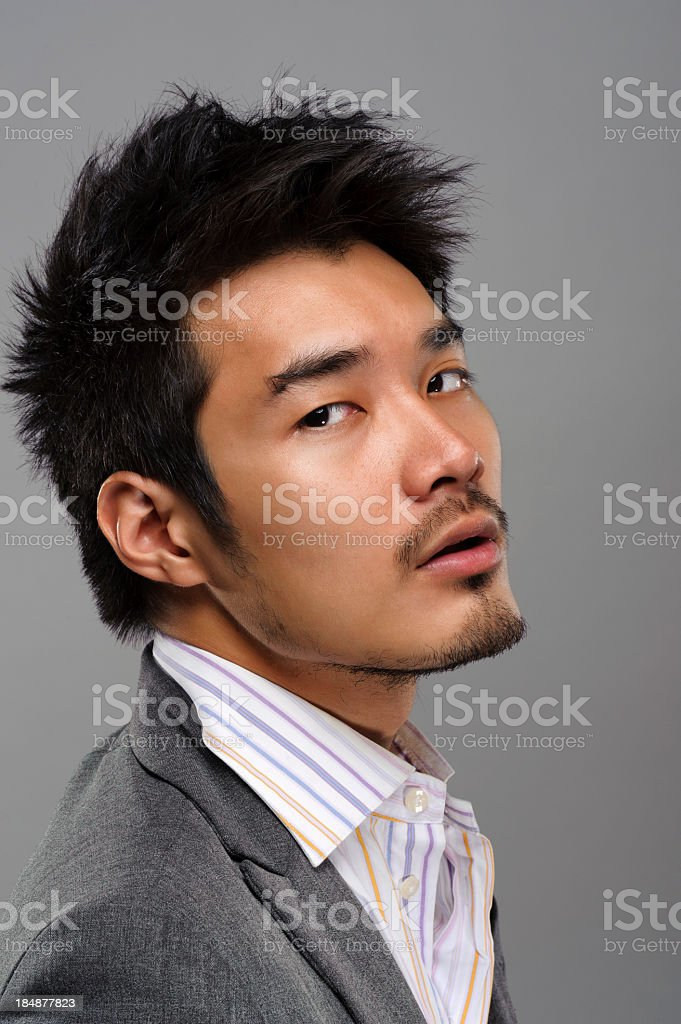 A handsome Asian man in a dress shirt and tuxedo stock photo