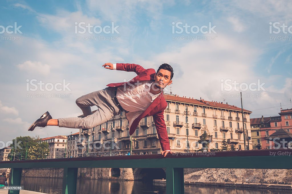 Handsome Asian model jumping in the city streets stock photo