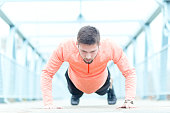 Handsome athlete doing a push-ups outdoor