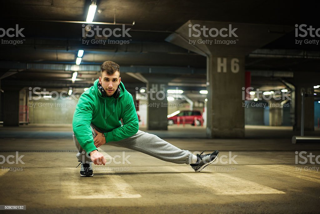 Handsome athlete stretching at parking garage. stock photo