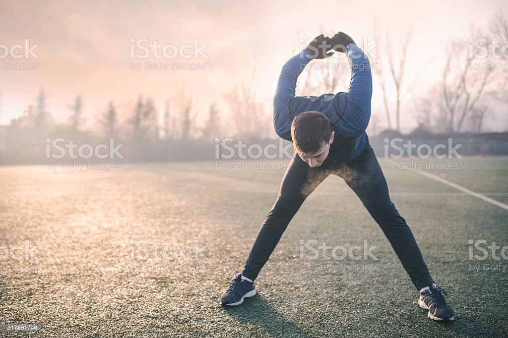 Handsome athlete warming up before jogging stock photo