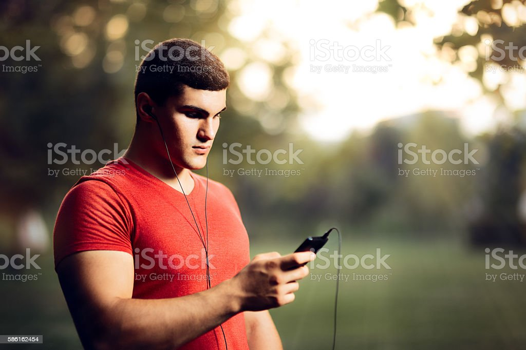 Handsome Athletic Man Wearing Earphones Holding His Smartphone stock photo