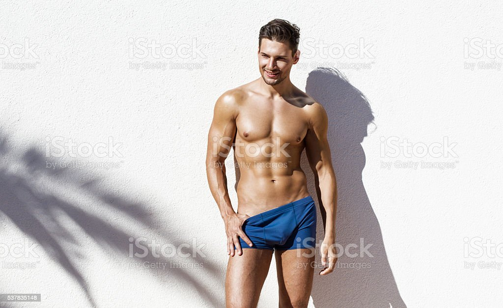 Handsome atletic man wearing swimming trunks stock photo